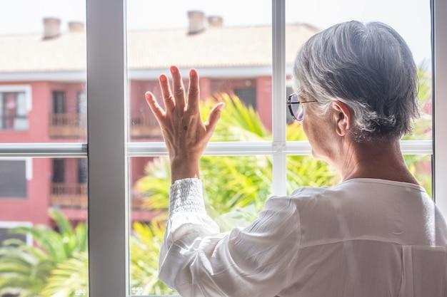 Mujer mayor quedarse en casa en la ventana mirando hacia afuera