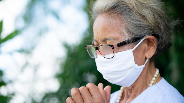 La mujer mayor está rezando con los ojos cerrados y la marca de la cara del desgaste en el fondo verde de la naturaleza