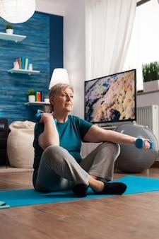 Mujer mayor en ropa deportiva calentando los músculos del brazo practicando ejercicios de bienestar con mancuernas