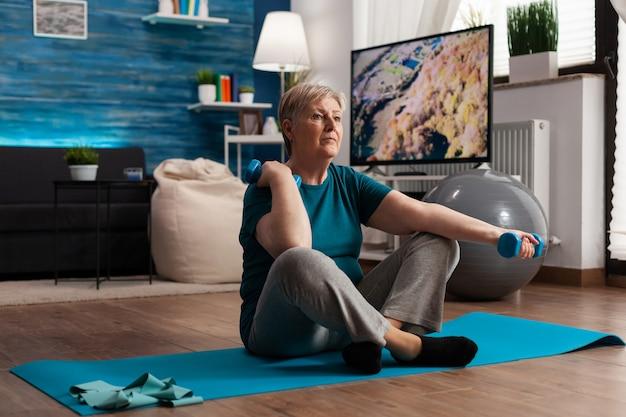Mujer mayor en ropa deportiva calentando los músculos del brazo practicando entrenamiento de bienestar con mancuernas pensión ...