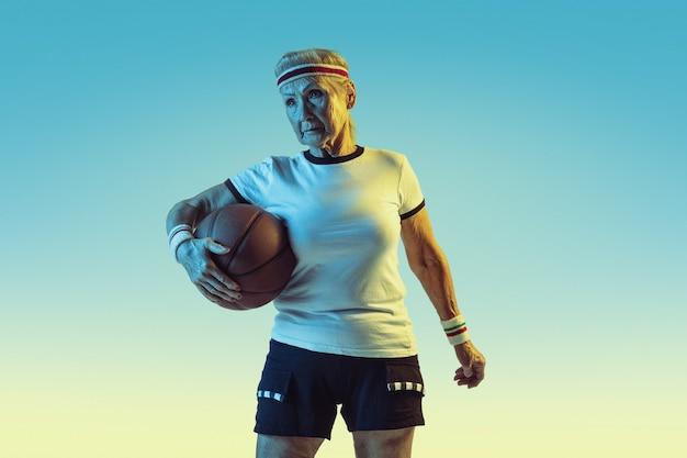 Mujer mayor en ropa deportiva jugando baloncesto sobre fondo degradado, luz de neón. modelo femenino en gran forma se mantiene activo. concepto de deporte, actividad, movimiento, bienestar, confianza. copyspace.