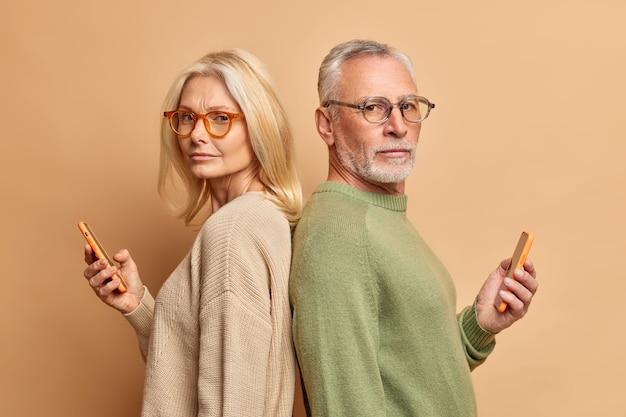 Una mujer mayor seria y su esposo sostienen aparatos modernos, leen los medios de comunicación, pasan tiempo libre en internet, se ignoran mutuamente, están de pie, usan gafas, suéter aislado sobre una pared beige.