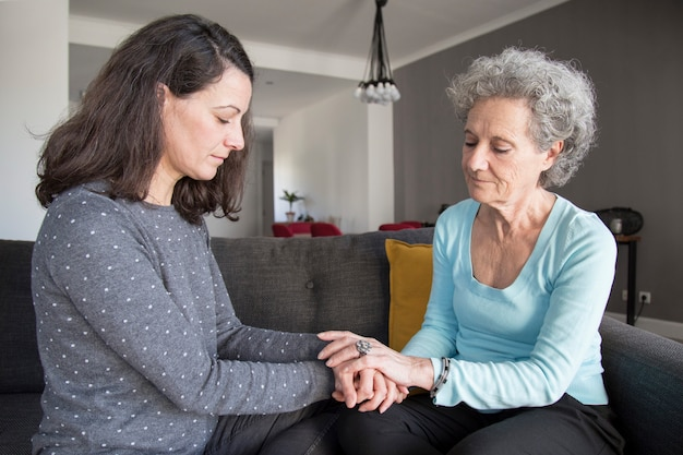 Mujer mayor seria y su hija tomados de la mano