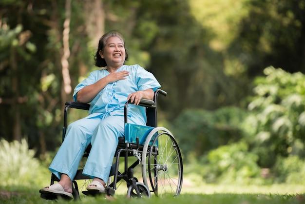 Mujer mayor solitaria sentada triste sensación en silla de ruedas en el jardín en el hospital