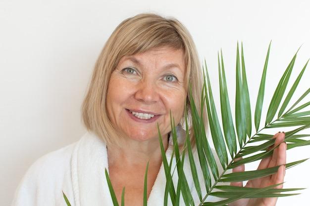 Mujer mayor sonriendo concepto anti-edad con hoja de palma. cara de mujer madura después del tratamiento de spa. vejez con alegría, clínica de cirugía plástica, abuela linda, cosmetología, nuevo senior, pensionista, gente madura