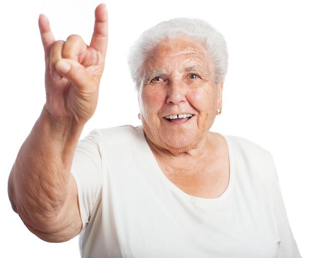 Mujer mayor sonriendo haciendo los cuernos con la mano