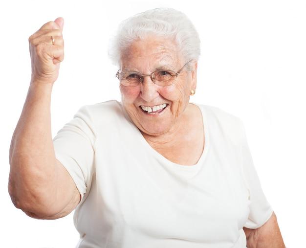 Mujer mayor sonriendo con un puño levantado