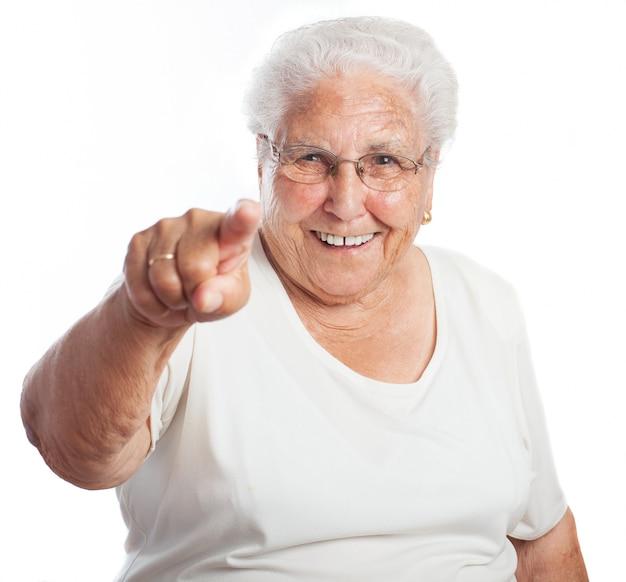 Mujer mayor sonriendo señalando hacia el frente