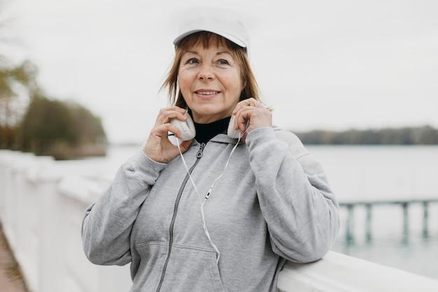 Mujer mayor sonriente con auriculares al aire libre mientras hace ejercicio