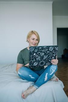 Mujer mayor sonriente casual atractiva feliz de la edad media que trabaja en una computadora portátil que se sienta en la cama en la casa.