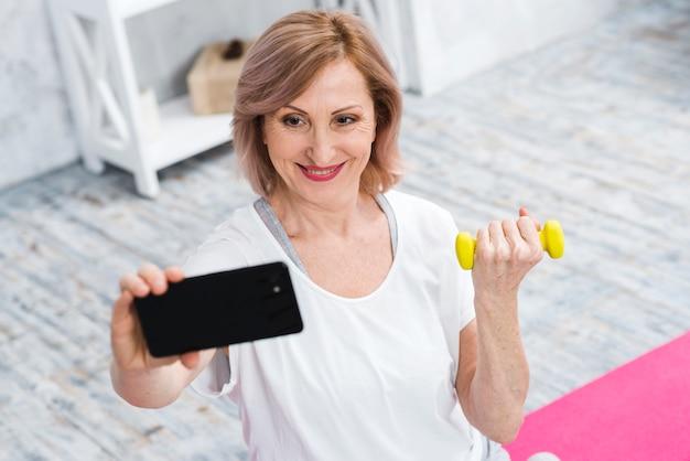 Mujer mayor sonriente con las pesas de gimnasia que toman el selfie usando el teléfono celular