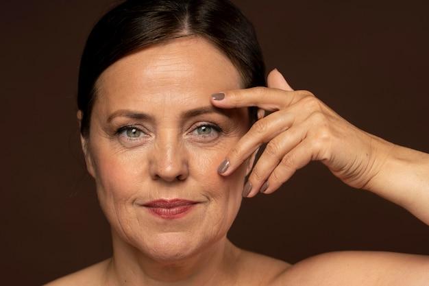 Mujer mayor sonriente posando con maquillaje y mostrando las uñas