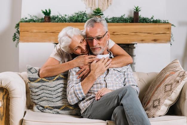 Mujer mayor sonriente que abraza a su marido de detrás que se sienta en el sofá