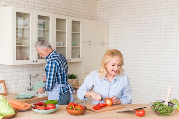 Mujer mayor sonriente que corta el pimiento rojo con el cuchillo que mira la tableta digital y su marido que lavan platos en el fregadero de cocina