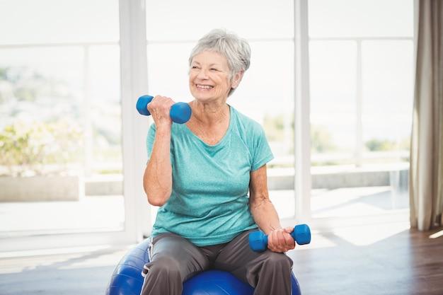Mujer mayor sonriente que lleva a cabo pesa de gimnasia