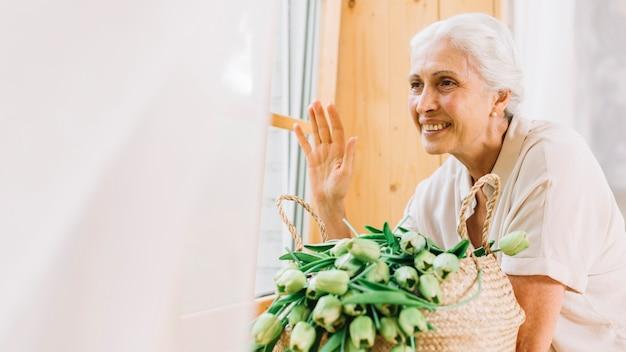 Mujer mayor sonriente que mira a través de la ventana que agita su mano