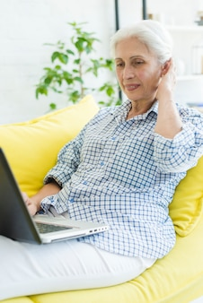 Mujer mayor sonriente que se sienta en el sofá que mira el ordenador portátil