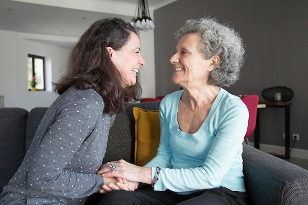 Mujer mayor y su hija divirtiéndose y tomados de la mano