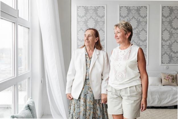 Mujer mayor y su hija madura mirando a la ventana