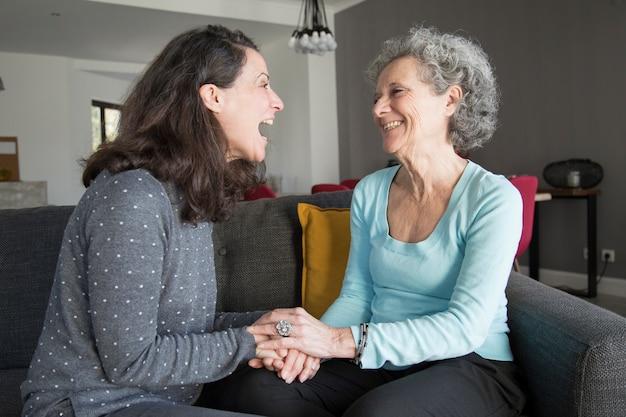 Mujer mayor y su hija riendo y tomados de la mano