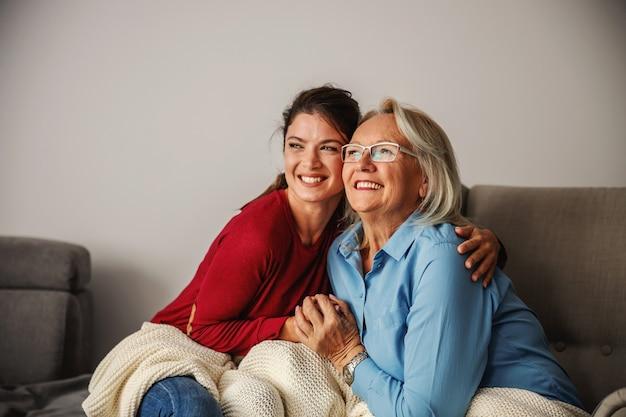 Mujer mayor y su hija sentada en casa y abrazándose.