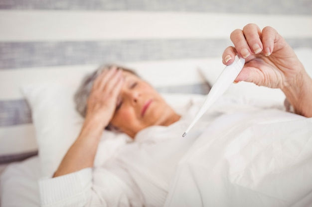 La mujer mayor sufre de fiebre que controla su temperatura en el termómetro
