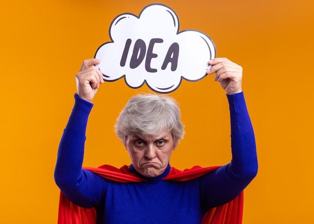 Mujer mayor superhéroe con capa roja sosteniendo el cartel de la burbuja del discurso con la idea de la palabra sobre su cabeza