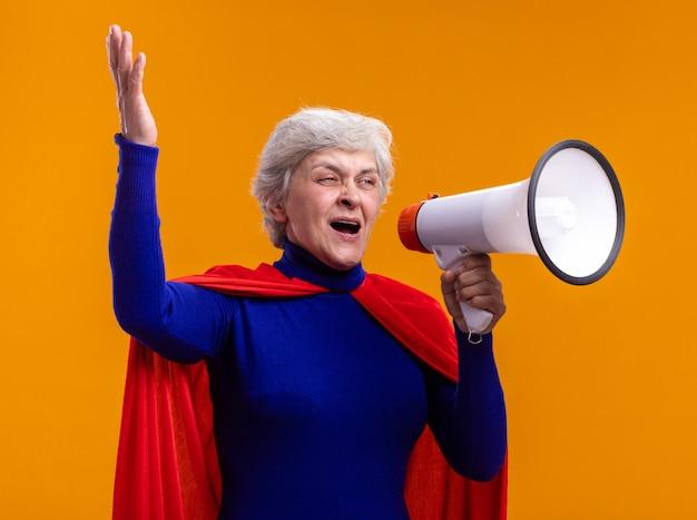 Mujer mayor superhéroe vistiendo capa roja gritando al megáfono feliz y emocionado de pie sobre fondo naranja