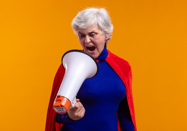 Mujer mayor superhéroe vistiendo capa roja gritando al megáfono frustrado de pie sobre naranja