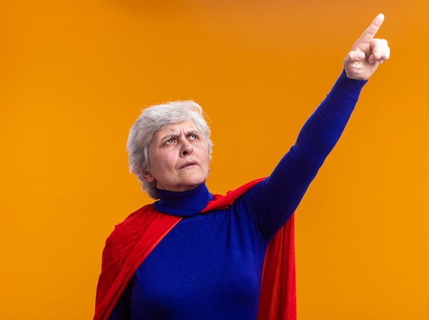 Mujer mayor superhéroe vistiendo capa roja mirando hacia arriba con el ceño fruncido apuntando con el dedo índice de pie sobre naranja