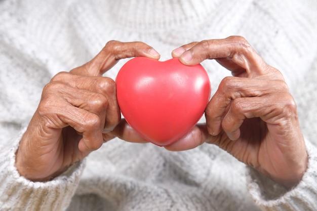 Mujer mayor, tenencia, corazón rojo, cicatrizarse