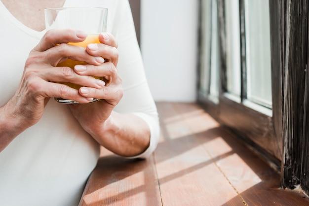 Mujer mayor tomándose un zumo