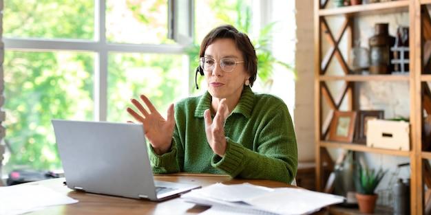 Una mujer mayor trabaja frente a un monitor de computadora portátil consultando sobre el llenado en línea de formularios de impuestos y docu ...