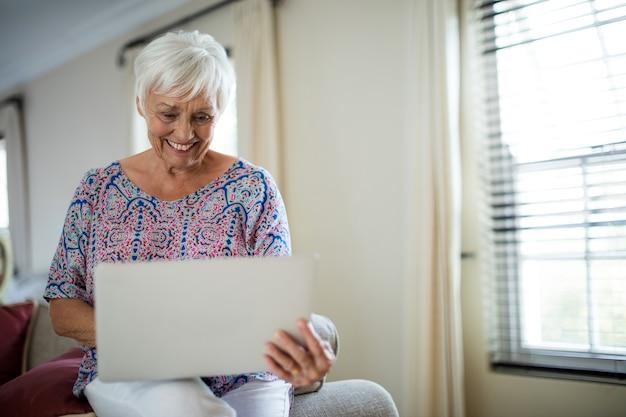 Mujer mayor, usar la computadora portátil, en, sala, en casa