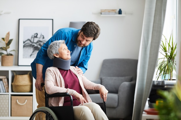 Mujer mayor con vendaje en el cuello sentado en silla de ruedas y hablando con el hombre en la habitación
