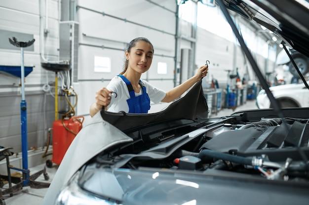 Mujer mecánica se encuentra en el capó en taller mecánico