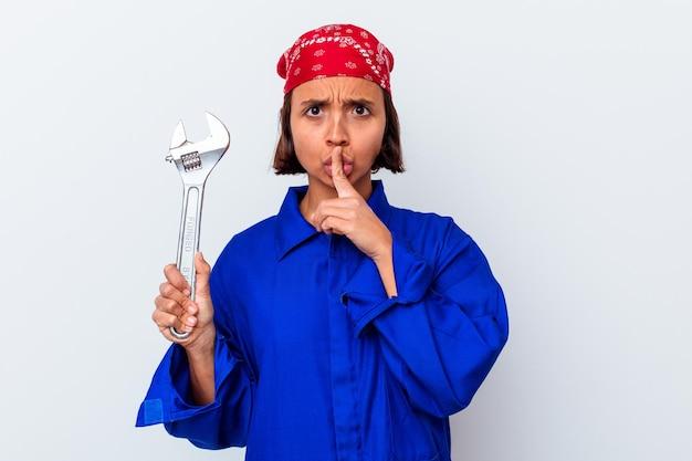 Mujer mecánica joven que sostiene una llave aislada que guarda un secreto o que pide silencio.