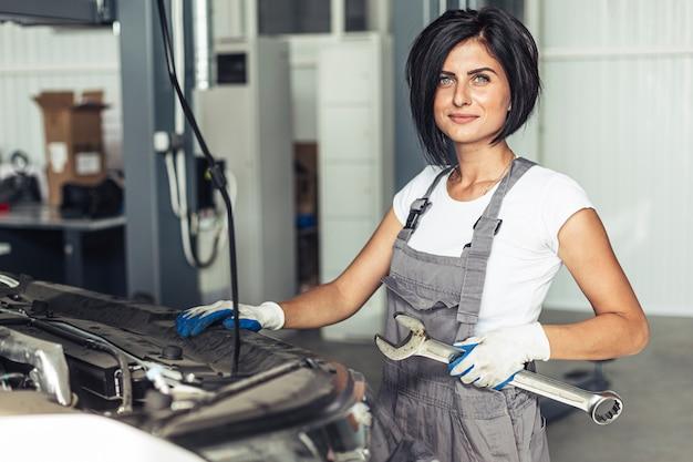 Mujer mecánica que sostiene la llave para arreglar el coche