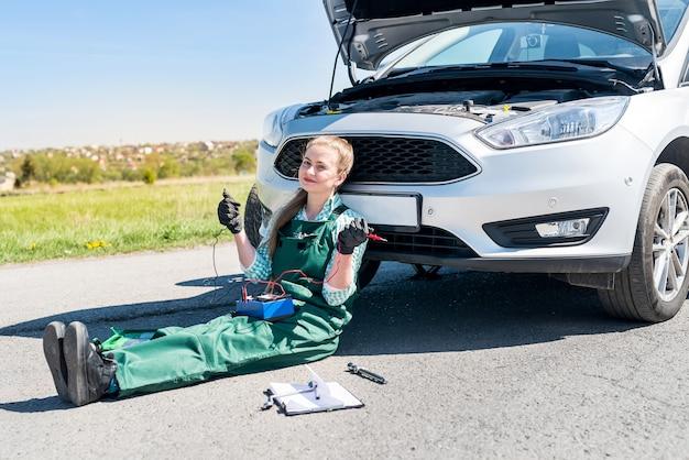 Mujer mecánico buscando problemas con el motor del coche