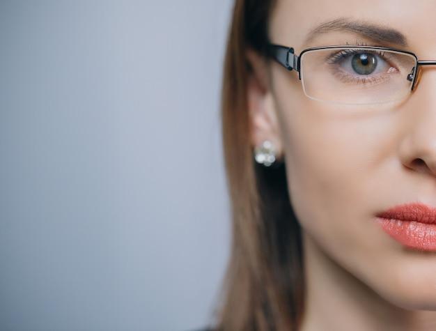 Mujer de media cara en glasess mira a la cámara. ciérrese para arriba del ojo femenino con los vidrios aislados en fondo con el espacio de la copia.