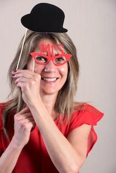 Mujer de mediana edad con accesorios divertidos de fotomatón