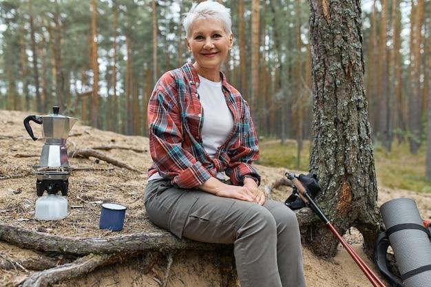 Mujer de mediana edad alegre activa sentada bajo un árbol con equipo de camping agua hirviendo para el té en el quemador de la estufa de gas, con un pequeño descanso durante la caminata de larga distancia. gente, aventura, viajes y senderismo