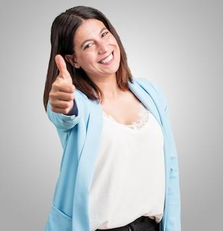 Mujer de mediana edad, alegre y emocionada, sonriendo y levantando su pulgar hacia arriba, concepto de éxito y aprobación, gesto aceptable