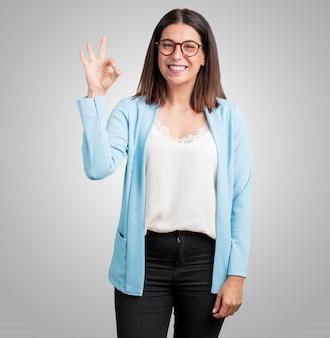 Mujer de mediana edad, alegre y segura, haciendo un gesto aceptable, excitada y gritando
