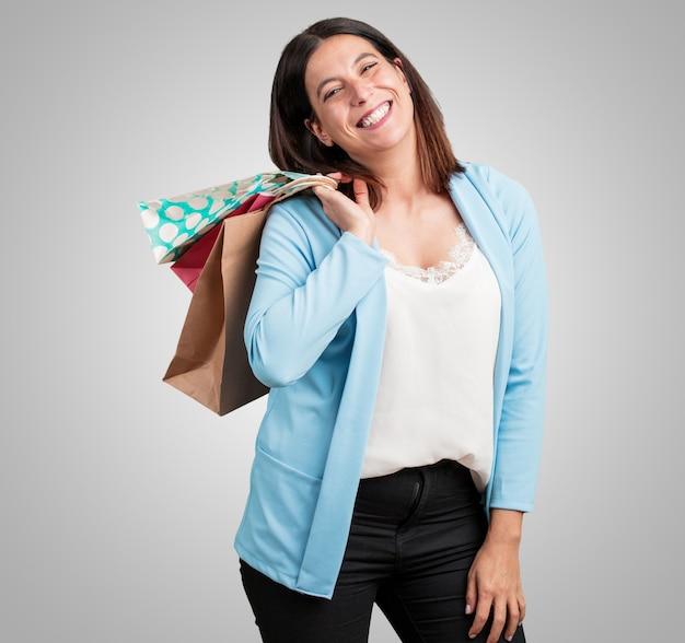Mujer de mediana edad, alegre y sonriente, muy emocionada llevando bolsas de la compra, lista para ir de compras y buscar nuevas ofertas.