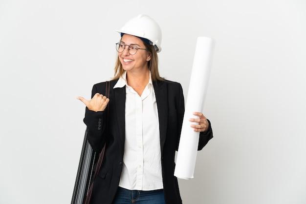 Mujer de mediana edad arquitecto con casco y sosteniendo planos sobre aislados apuntando hacia el lado para presentar un producto