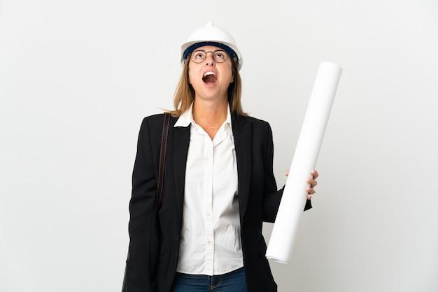 Mujer de mediana edad arquitecto con casco y sosteniendo planos sobre aislados mirando hacia arriba y con expresión de sorpresa