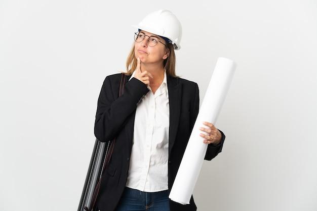 Mujer de mediana edad arquitecto con casco y sosteniendo planos sobre aislados teniendo dudas mientras mira hacia arriba
