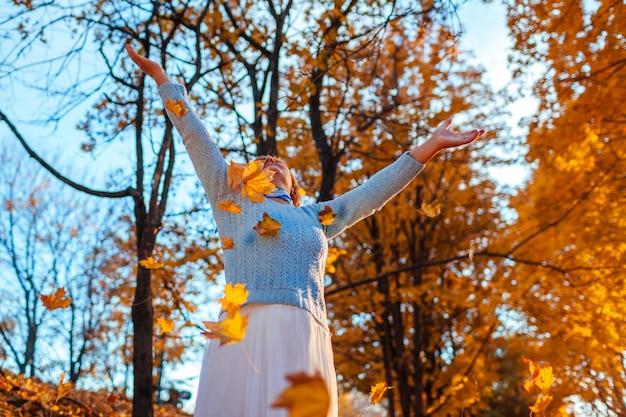 Mujer de mediana edad arrojando hojas en el bosque de otoño mujer senior divirtiéndose