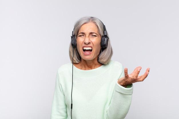 Mujer de mediana edad con aspecto enojado, molesto y frustrado gritando wtf